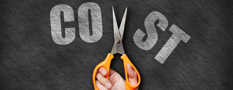 Hand holding orange scissors cutting cost text on blackboard background