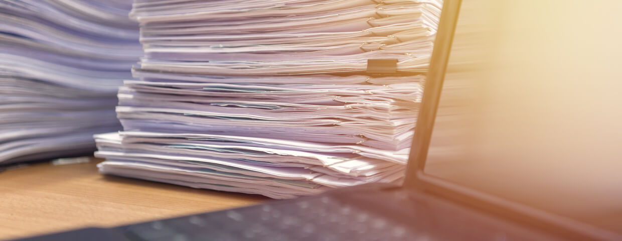 Stack of documents next to laptop