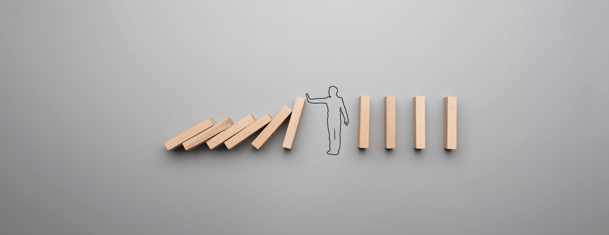 Wide cropped image of the outline of a businessman stopping the domino effect on gray background.