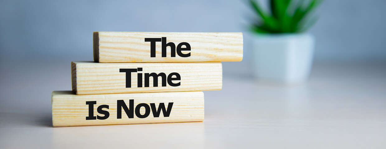 Wooden blocks stacked on top of each other with the words the time is now in black writing on them