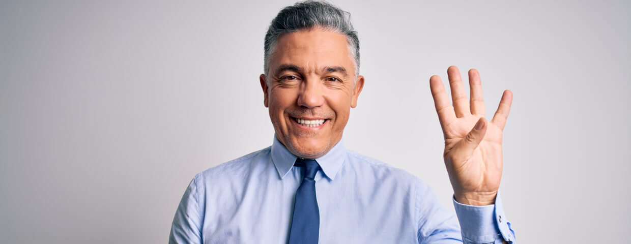 Business man smiling and holding up four fingers